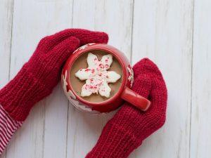 Ciocolata calda cu fulg de nea in cana de ceramica tinuta cu manusi