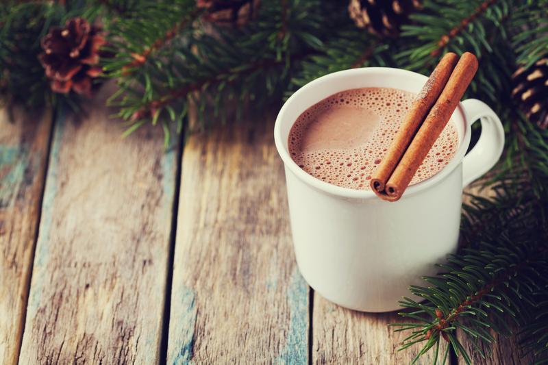 Ciocolata calda cu scortisoara in cana alba langa brad